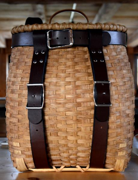 A  stained (finished) Adirondack Pack Basket with leather harness