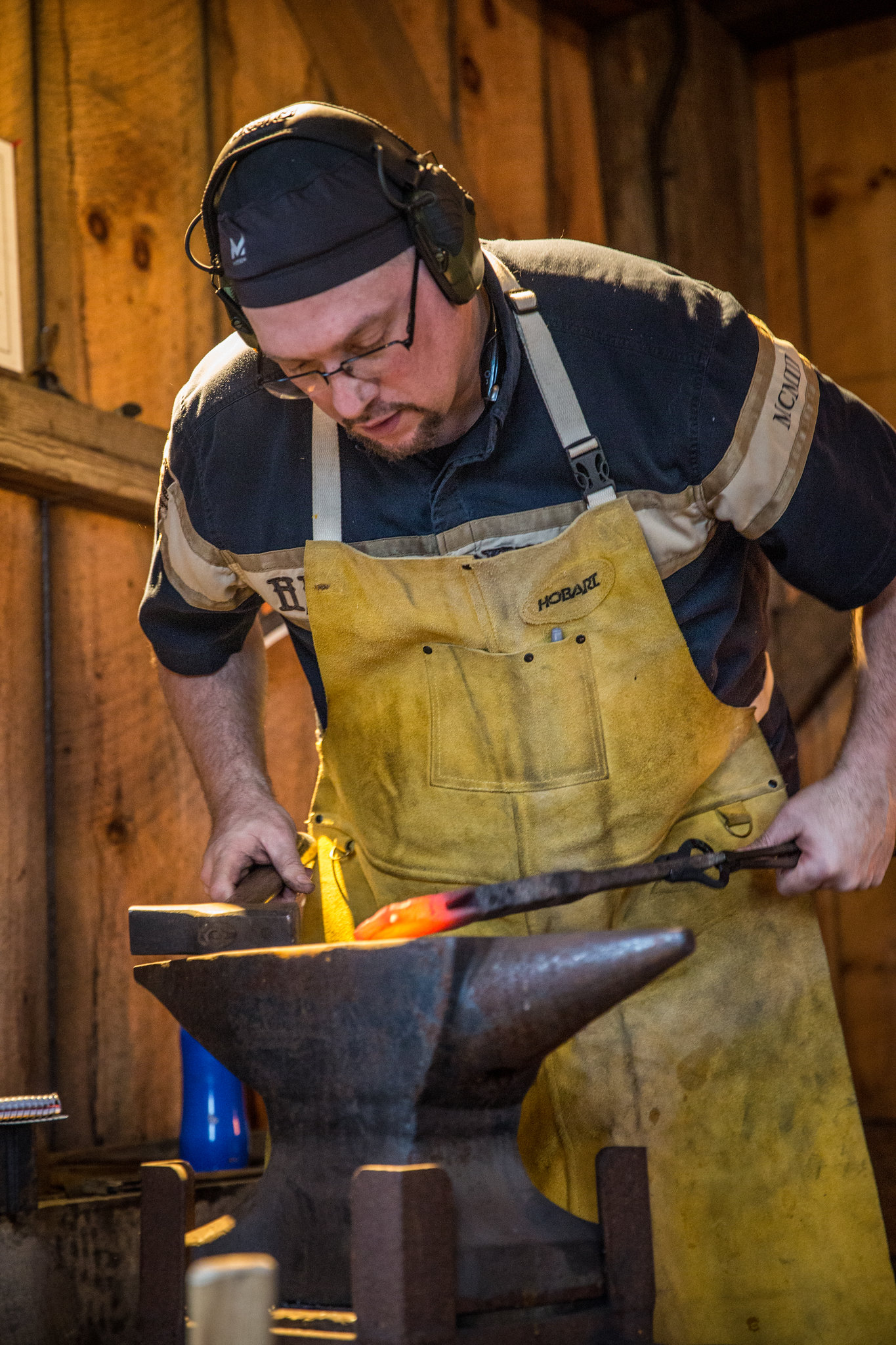 A blacksmithing student works at an anvil